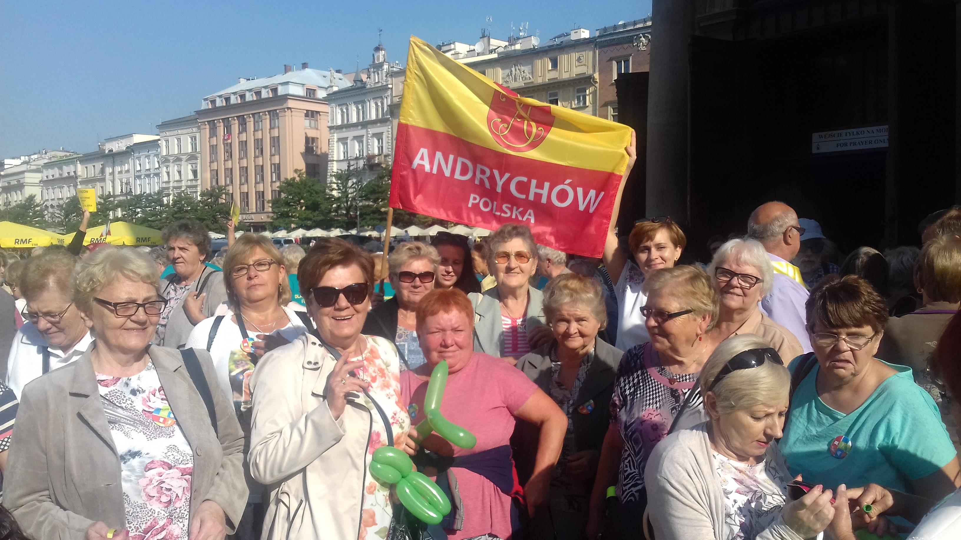 Zdjęcie grupy seniorów stojących na Rynku Głównym w Krakowie. Trzymają żółto-czerwoną flagę z herbem Andrychowa i napisem Andrychów Polska.