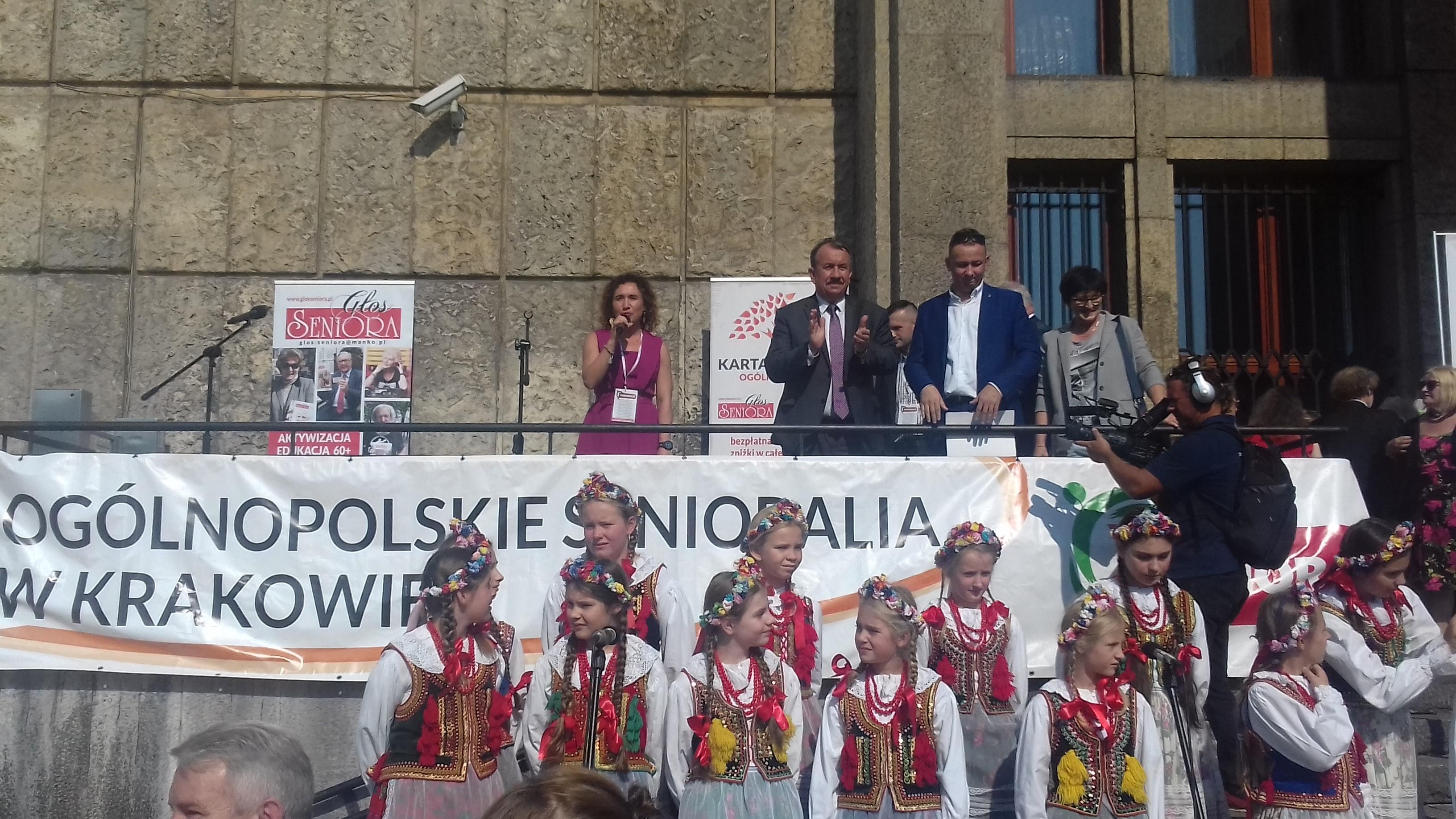Zdjęcie grupy dziewczynek ubranych w stroje krakowskie, w tle napis Ogólnopolskie Senioralia w Krakowie.