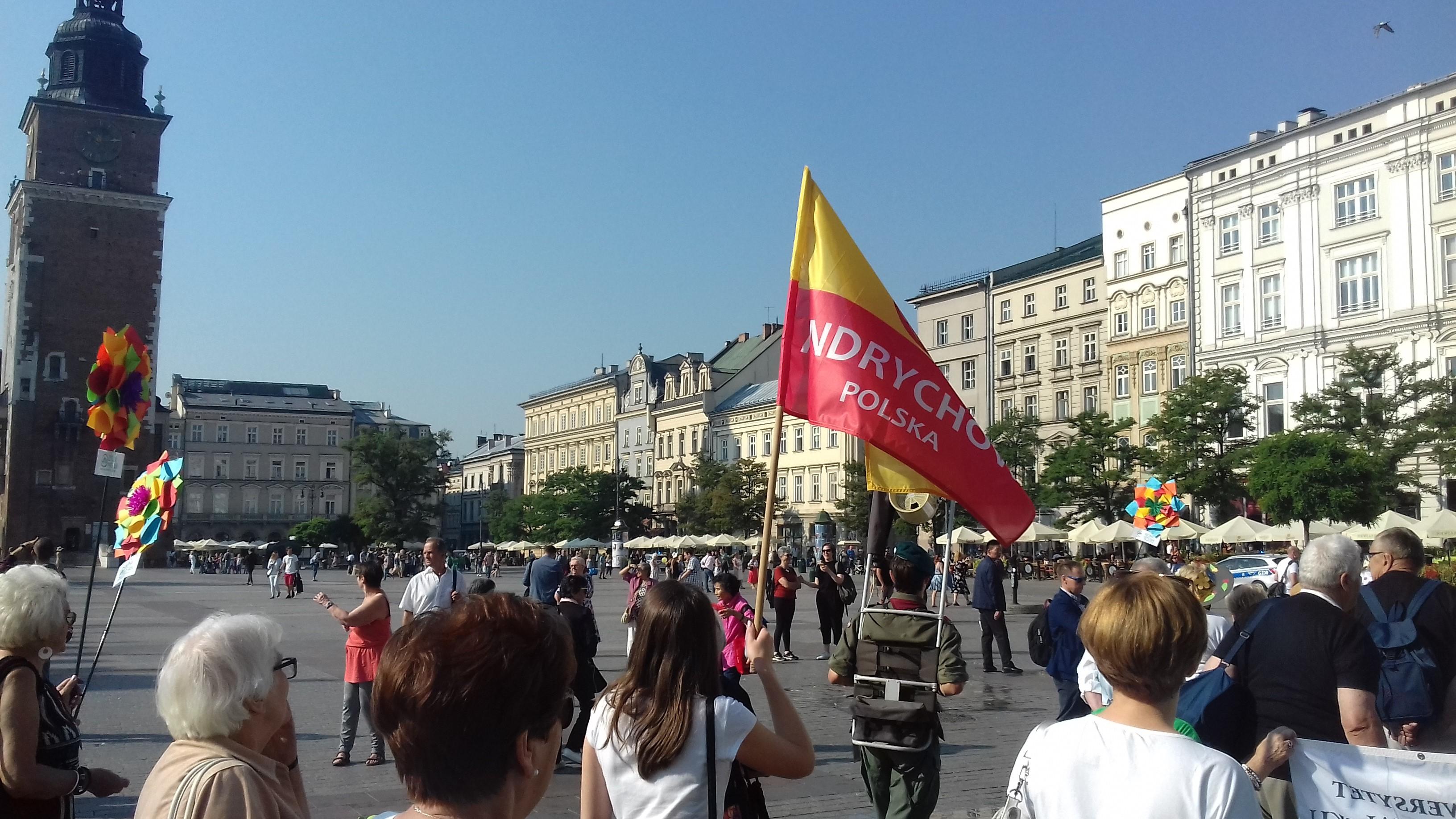 Na zdjęciu grupa seniorów idących przez Rynek Główny w Krakowie.