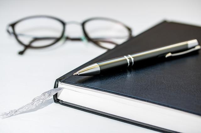 Na zdjęciu zamknięty zeszyt, na nim długopis, obok okulary
