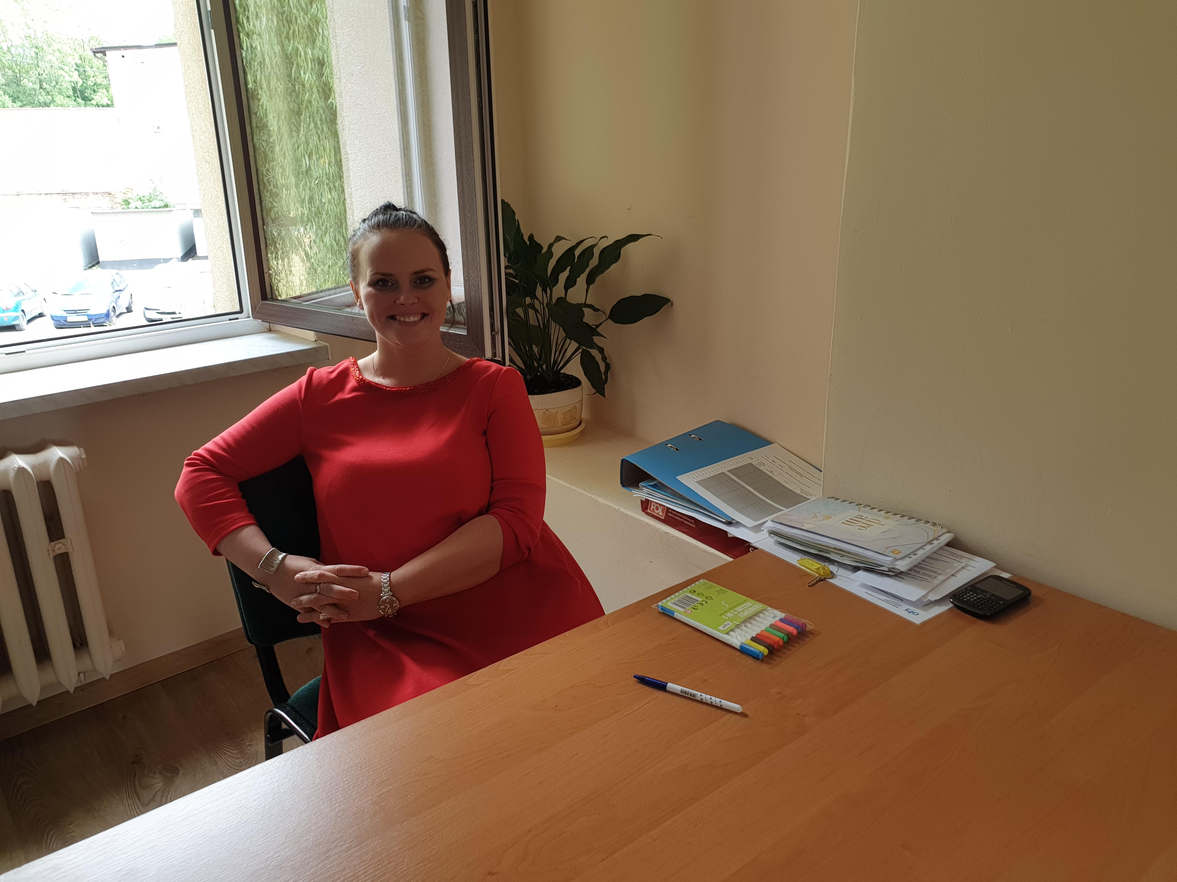 Zdjęcie Moniki Pleszewskiej siedzącej w gabinecie