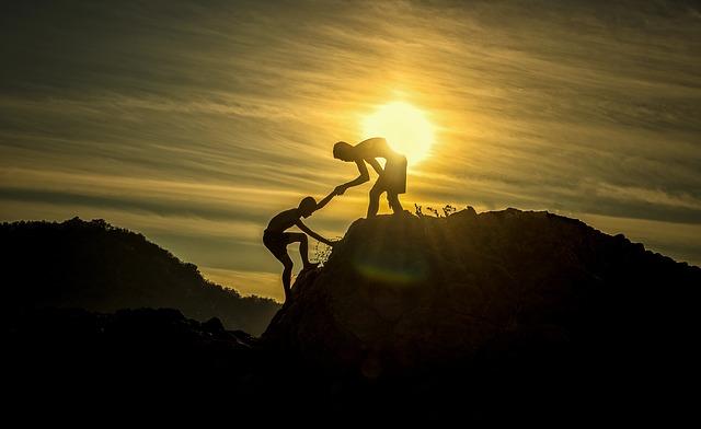 Na zdjęciu zarys gór na tle zachodzącego słońca. Po zboczu wspina się człowiek, na szczycie stoi drugi, który trzyma go za rękę i pomaga wejść na górę.