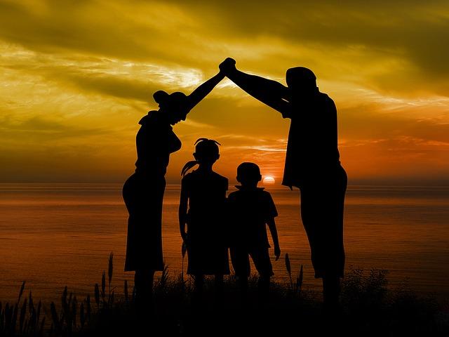 Rodzina na tle zachodzącego słońca. Rodzice trzymają się za ręce podniesione nad głowami - ich sylwetki tworzą kształt domu ze szpiczastym dachem. W środku stoją dzieci.