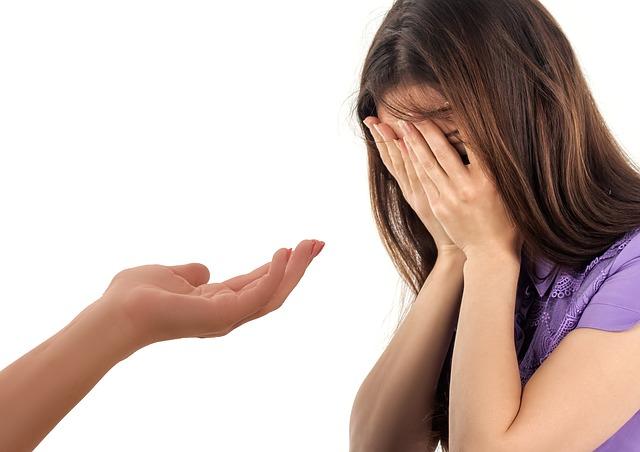 Na zdjęciu płacząca kobieta, obok ktoś wyciąga do niej rękę, oferując wsparcie