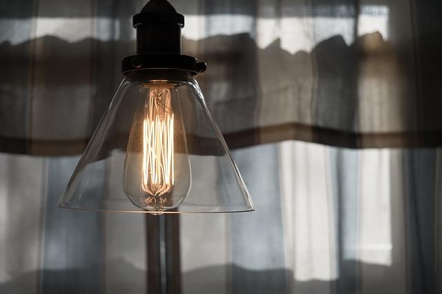 Wnętrze domu. Zbliżenie na lampę, w tle okno z firanką