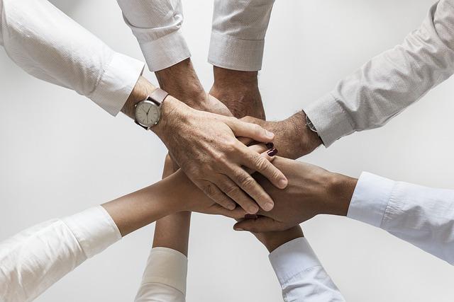 Zdjęcie kilku osób - każda z nich kładzie dłoń na dłoni innej osoby, jak drużyna przed meczem
