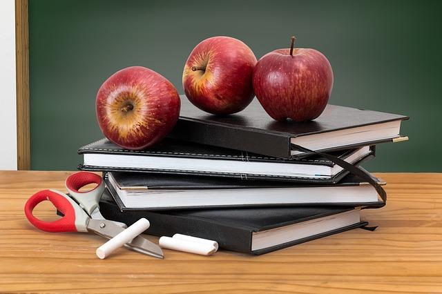Wnętrze klasy szkolnej. Na pierwszym planie biurko, na nim zeszyty, kreda, nożyczki i jabłka, w tle szkolna tablica