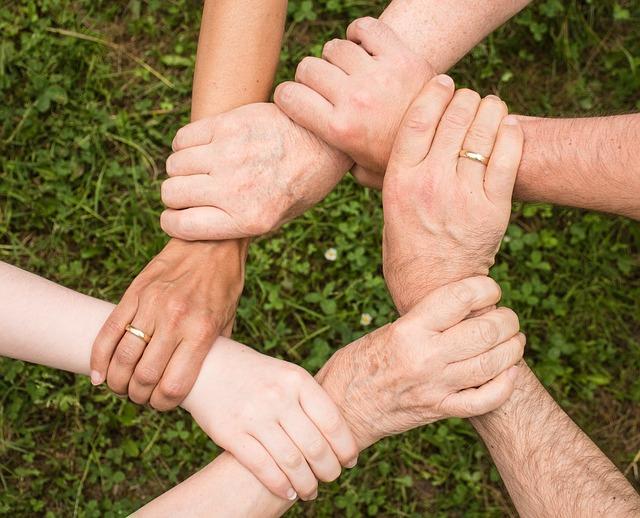 Koło utworzone z dłoni kilku osób, które wspierają się wzajemnie