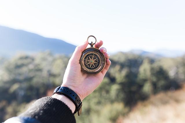 Ręka osoby, która trzyma kompas, w tle góry
