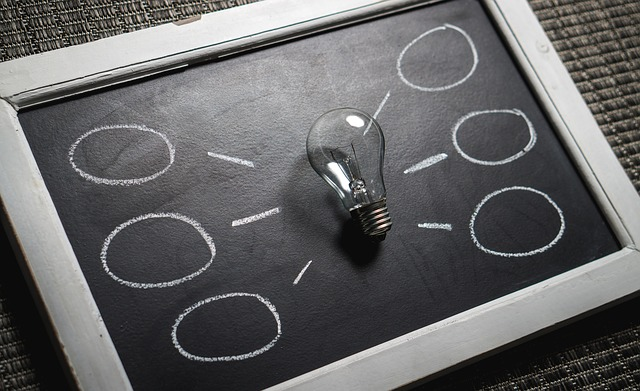 Na zdjęciu tabliczka do pisania, na niej żarówka, po obu stronach żarówki narysowane dymki symbolizujące pomysły
