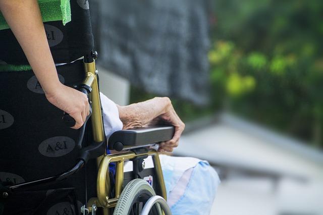Osoba poruszająca się na wózku inwalidzkim, za nią osoba, która pcha wózek