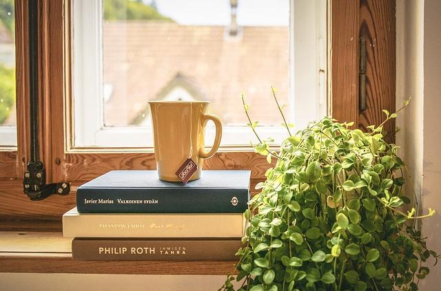 Fragment drewnianego okna z parapetem, na parapecie książki ułożone jedna na drugiej, na nich kubek z herbatą, a obok doniczka z zieloną rośliną.