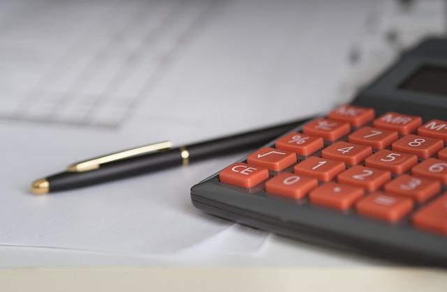 Na zdjęciu kalkulator i długopis, w tle kartki z tabelkami