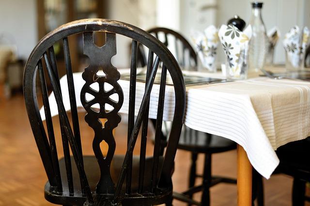Wnętrze domu. Na pierwszym planie stół z krzesłami.