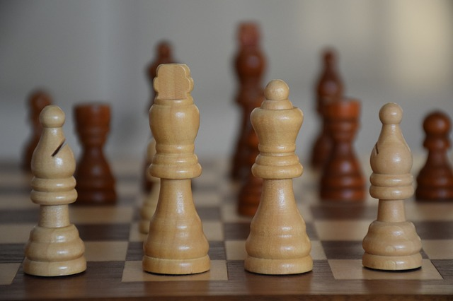 Na zdjęcie szachownica, na niej figurki szachowe w pozycji wyjściowej