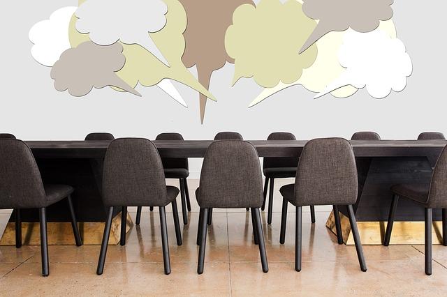Sala konferencyjna. Na środku stół, wokół krzesła, na ścianie namalowane dymki symbolizujące pomysły