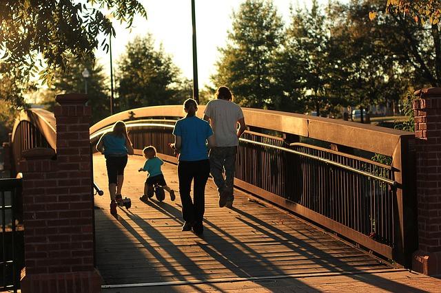 Na zdjęciu rodzina - rodzice i dwoje dzieci, którzy przechodzą przez most