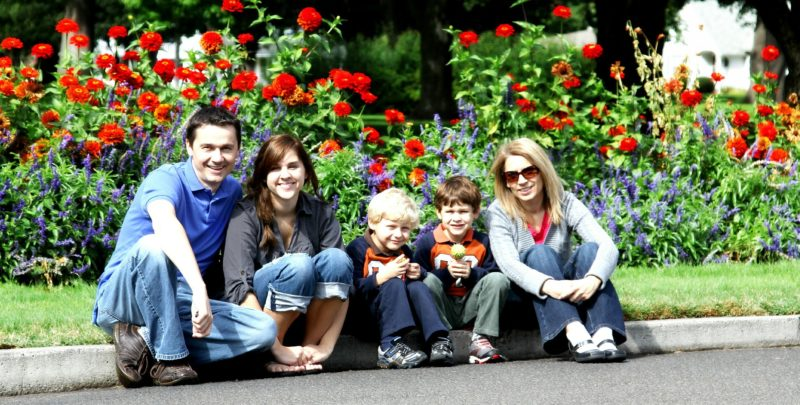 Rodzina - rodzice i troje dzieci. Wszyscy siedzą na krawężniku, za nimi park.