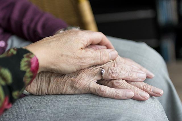 Na zdjęciu dłonie starszej kobiety. Inna osoba obejmuje je swoją dłonią, w geście wsparcia