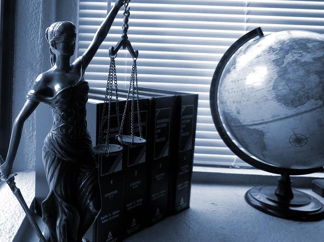 Biurko, na nim globus, grube książki i figurka Temidy - bogini sprawiedliwości - trzymającej wagę