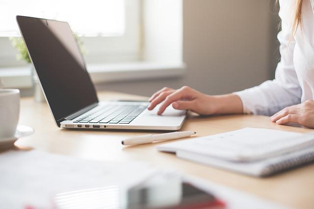 Na zdjęciu kobieta w białek koszuli siedzi przy biurku i pracuje przy komputerze