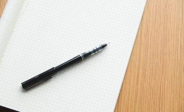 Na zdjęciu otwarty zeszyt w kratkę, na nim długopis