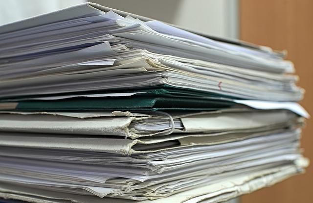 Zdjęcie stosu teczek z dokumentami i pojedynczych kartek