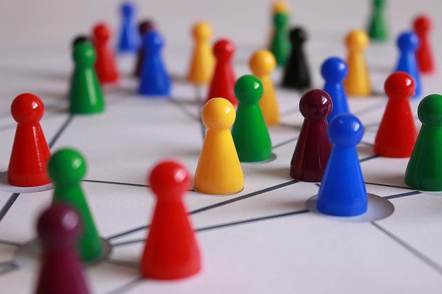 Pionki do gry przypominające kształtem sylwetki ludzi. Stoją na planszy z polami, między niektórymi z nich są linie, które mogą symbolizować interakcje
