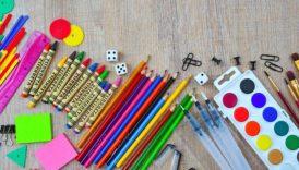 Na zdjęciu stół, na nim kredki ołówkowe i woskowe, długopisy, farby i pędzle, karteczki samoprzylepne, kostki do gry, spinacze biurowe