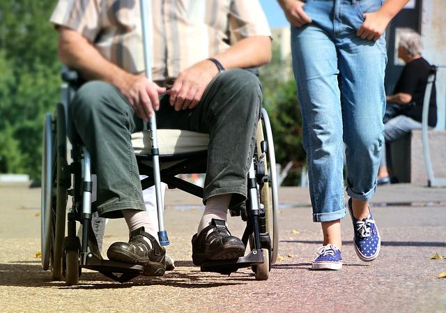Mężczyzna poruszający się na wózku inwalidzkim, towarzyszy mu zdrowa osoba