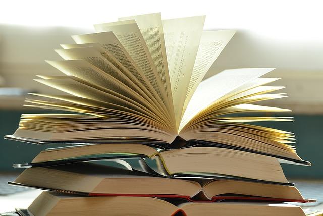 Stos otwartych książek, ułożonych jedna na drugiej.