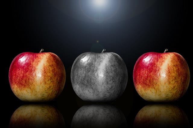 Zdjęcie trzech jabłek ustawionych w szeregu. Jabłka po lewej i prawej stronie są kolorowe, a owoc w środku czarno-biały.