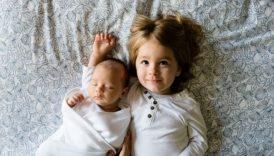 Zdjęcie przytulonych dzieci leżących na łóżku. Jedno jest w wieku przedszkolnym, drugie to niemowlę