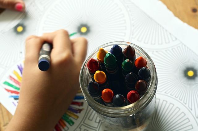Na zdjęciu zbliżenie na rękę, która koloruje kolorowankę kredkami woskowymi. Obok słoik z kredkami.
