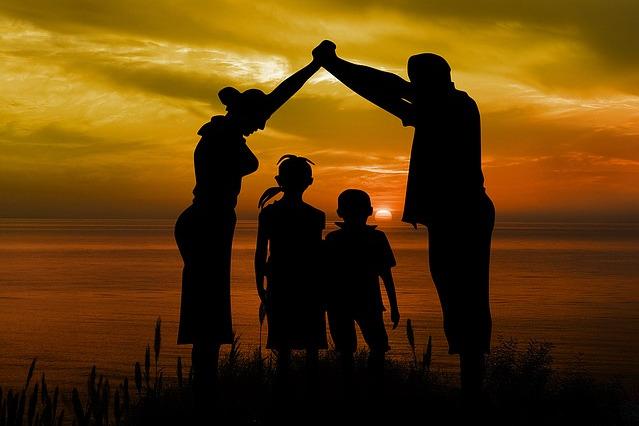 Na zdjęciu rodzina na tle zachodzącego słońca. Rodzice trzymają się za ręce podniesione nad głowami - ich sylwetki tworzą kształt domu ze szpiczastym dachem. W środku stoją dzieci.