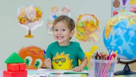 Zdjęcie uśmiechniętego chłopca, który siedzi przy biurku i pisze coś w zeszycie długopisem. Na biurku są jeszcze: globus, kredyt, klocki, farby i pędzle.