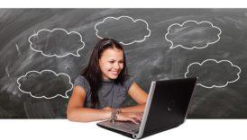 Zdjęcie młodej dziewczyny pracującej przy komputerze z uśmiechem na ustach. Za nią szkolna tablica z narysowanymi kredą dymkami symbolizującymi pomysły