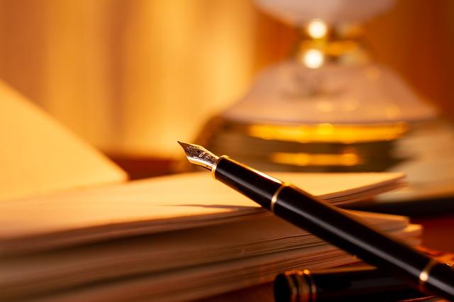 Zdjęcie wiecznego pióra opartego o otwarty zeszyt leżący na biurku.