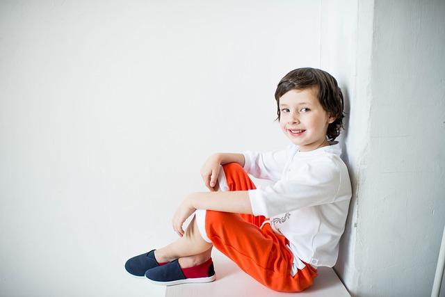 Zdjęcie uśmiechniętego chłopca siedzącego na podłodze, opartego o ścianę