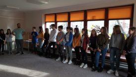 Na zdjęciu młodzież stoi w kole, w sali świetlicowej. Między nastolatkami trener prowadzący szkolenie.