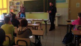 Dzieci w sali lekcyjnej, przy tablicy policjant, który prowadzi lekcję