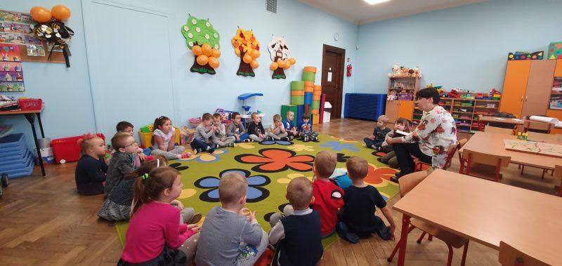 Na zdjęciu sala w przedszkolu. Dzieci siedzą na dywanie w kręgu, obok nich dyrektor Dyrektor Miejskiej Biblioteki Publicznej w Andrychowie, Sylwia Błasiak, która opowiada dzieciom bajkę.