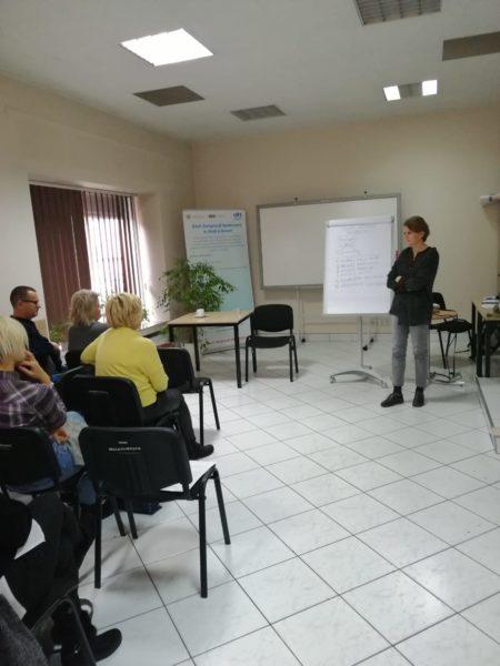 Na zdjęciu sala, w której trwa szkolenie - osoba prowadząca stoi na środku, słuchają jej siedzący na krzesłach uczestnicy szkolenia.