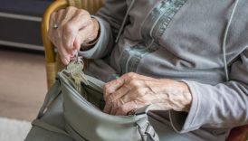 Na zdjęciu starsza kobieta chowa klucze do torebki