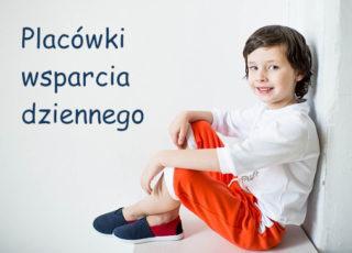 """Na zdjęciu chłopiec siedzi przy ścianie, na podłodze, uśmiecha się. Obok napis: """"Placówki wsparcia dziennego"""""""