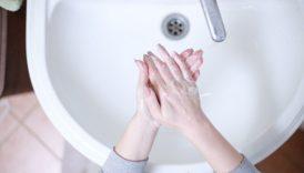 Zdjęcie osoby, która myje ręce nad umywalką