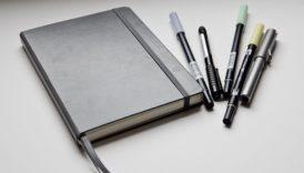 Na zdjęciu zamknięty notes, obok długopisy