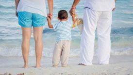 Na zdjęciu mama, tata, w środku dziecka. Stoją nad brzegiem morza, trzymają się za ręce