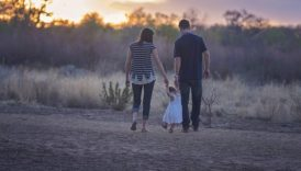 Rodzina - mama i tata, pomiędzy nimi mała córeczka, którą trzymają za ręce