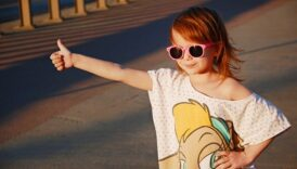Uśmiechnięta dziewczynka w okularach przeciwsłonecznych, stoi przy drodze z kciukiem podniesionym do góry